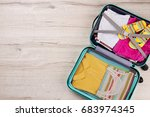 Small photo of Full opened suitcase, wooden surface. Bag packed with clothing, top view. Concept of summer vacation.