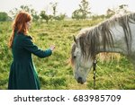 A Woman Is Feeding A Horse In...