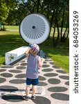 Small photo of June, 2017. Krakow. Poland. Museum of Science in the open air. Park. Sweet little boy operating principle of optical illusion device. STEM education. Back to school.