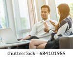 two asian coworkers use laptop... | Shutterstock . vector #684101989