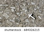 Small photo of A Christian metal cross against a background of stone crumbs. Religious symbol. Catholicism, Protestantism, Orthodoxy. Vera.