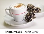 Cup of cappuccino coffee with chocolate candy - stock photo