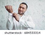 man takes on white shirt... | Shutterstock . vector #684533314