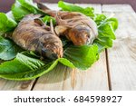 Small photo of The smoked baked fish is laid out on green leaves lying on coarse unglued boards. Home healthy eating at a picnic