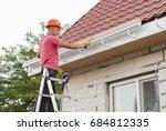 worker installs the gutter... | Shutterstock . vector #684812335