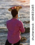 Small photo of View from the back young musician play the trumpet on rocky sea coast during surf. Tuba instrument.