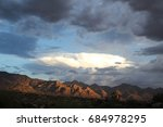 Small photo of Unusual long white cloud lit up from within hovering over the red Pusch Ridge mountains at sunset during monsoon season in the Tucson Arizona desert