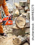Small photo of Lumberjack logger worker in protective gear cutting firewood timber tree in forest with chainsaw