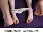 Stock photo female and male feet lie on a violet sheet women s panties are down on their feet lovers have sex 685032325