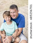 father and son cuddling on the... | Shutterstock . vector #685256701