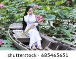 Small photo of Ho Chi Minh City, Vietnam - July 16th, 2017: Vietnamese girl in traditional long dress or Ao Dai inside boat floating in lotus pond is coy as to maintain their youth time in Ho Chi Minh City, Vietnam