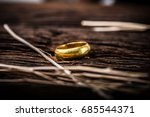 Golden ring on wooden background.