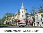 """Small photo of Ussuriysk, Russia, May, 19, 2016. Car near the monument of architecture of the late 19th century - Department store of the trading house """"Kunst and Albers"""" in the historical centre of Ussuriysk"""