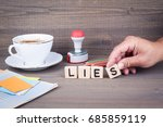 Small photo of lies. Wooden letters on dark background
