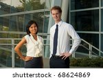 A pair of happy and smiling business professionals stand outside of a glass office building.  20s female Asian Thai model of Chinese descent and 20s handsome caucasian male British model. - stock photo
