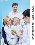 Dentist gives Apple a child in the dental office - stock photo