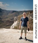 Small photo of HIERVE EL AGUA, OAXACA, MEXICO - JANUARY 15, 2015: YOUNG MAN IN FRONT OF PETRIFIED WATERFALL AT Hierve el Agua, a set of natural rock formations that resemble cascades of water.