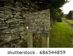Small photo of Indecipherable White Writing On Old Wooden Sign