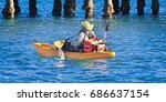 Fisherman with fishing gear paddling a Kayak in blue water near a jetty. Coffs Harbour, New South Wales, Australia.   - stock photo