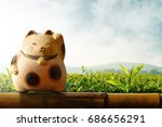 Stock photo japan maneki neko or beckoning cat mascot of lucky and money present over bamboo fence and green 686656291