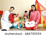 Handsome doctor and charming nurse take care and play with preschool boy and girl group on playground in hospital, visit for examination and relaxing patient.