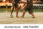 Small photo of An action picture of an old ball and foot of a kid who is playing football for exercise.Low key style.