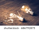 Small photo of Broken and Glowing light bulb comparison concept, problem and solution, failure and success, learning from mistake