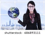 businesswoman is holding earth... | Shutterstock . vector #686893111