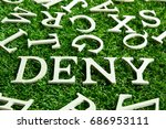 Small photo of Wording deny on artificial green grass with another english alphabet background