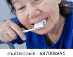 Small photo of Asian elderly woman trying use toothbrush ,hand tremor . Dental health