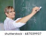 Senior Female Teacher Writing...