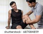 therapist treating injured knee ... | Shutterstock . vector #687084859