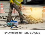 Male worker with safety equipments drilling concrete repairing driveway surface with jackhammer,danger sign concept.  Professional worker. - stock photo