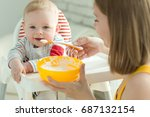 a woman is feeding a child  | Shutterstock . vector #687132154