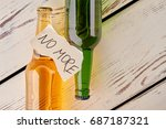 Small photo of Alcohol abuse, how to stop. Full bottles of alcohol beverages, torn papers sheet with text, old floor. Ways to beat booze.