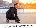 a beautiful young woman tying... | Shutterstock . vector #687256315