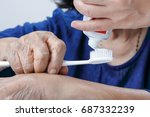 Small photo of Asian elderly woman trying use toothbrush ,hand tremor . Dental