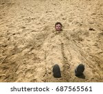 Small photo of A boy of 10 years in the sand. A child buried in the sand