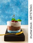 Small photo of Summer dessert from two layers: from chocolate mousse and pudding from chia in a glass cup on a wooden board , on a blue background. With fresh cherries on top, healthy food
