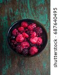 Small photo of frozen berries, black currant, red currant, raspberry, blueberry in ceramic bowl on rustic wooden table