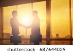 Small photo of silhouettes two businessmen handshake in cooperation agreement concept at office and successful business partner. business man shaking hands to seal a deal with his partner