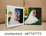 Small photo of Pages of wedding photobook or wedding album on the sofa with cushions.