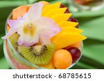 Closeup of serving of fresh tropical fruit salad in cocktail glass. Kiwi, melon, papaya, mango, red grapes, strawberry and orchid flower. - stock photo