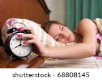 Young sleeping female turns alarm clock off  (woman out of focus) - stock photo