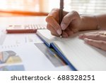 Small photo of Businessman writing on notebook on wooden table, People are recording accounting data calculated from calculator. To report information to the CEO. Concept finance planing and analyzes management.