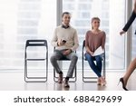 Small photo of Confident businesswoman walking by male and female job candidates sitting on chairs, following her with their eyes, fake artificial smile, pretending amiability, mask of pretense, social artifice
