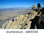 Several people climbing along rocky ridge on a trail - stock photo