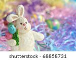 Easter background with wooden bunny figurine.  Pastel colored grass and painted eggs in background.  Macro with shallow dof. - stock photo