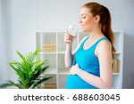 pregnant woman drinking water | Shutterstock . vector #688603045