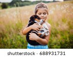 Stock photo little girl holds a puppy on her arms 688931731